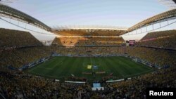 FILE - National soccer players from Brazil (L) and Croatia enter the stadium before their 2014 World Cup opening match at the Corinthians arena in Sao Paulo, June 12, 2014.