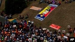 """Partidarios del líder de la oposición encarcelado Leopoldo López, llevan carteles que dicen """"No más dictadura"""" cerca de una bandera de López durante un mitin en Caracas, Venezuela, el sábado 18 de febrero de 2017."""