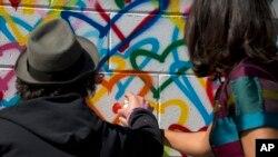 Michelle Obama y el artista Mr. Brainwash pintan un mural en el Día Internacional de la Mujer en Washington D.C., en honor del programa Let Girls Learn, que lidera la Primera Dama. Marzo 8 de 2016.
