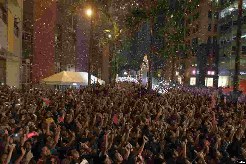 Confetti falls on revelers as they watch fireworks in the sky during New Year celebrations in Manila, Philippines, Jan. 1, 2015.