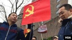 在紐約聯合國大樓前的抗議者。中共黨旗下面掛著象徵腐敗的魚肉圖片(美國之音章真拍攝)