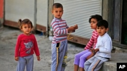 FILE - Syrian refugee children pass time in a neighborhood of the city of Gaziantep, southeastern Turkey.