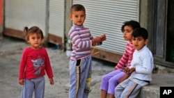 FILE - Syrian refugee children pass time in a neighborhood of the city of Gaziantep, southeastern Turkey on May 16, 2016.