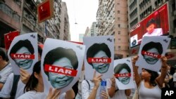 Protesters hold pictures of Hong Kong Chief Executive Carrie Lam as protesters march along a downtown street against the proposed amendments to an extradition law in Hong Kong Sunday, June 9, 2019.19.