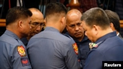 Philippine National Police chief Director-General Ronald dela Rosa (2nd-R) talks to fellow police officers during a Senate hearing regarding people killed during a crackdown on illegal drugs in Pasay, Metro Manila, Philippines, Aug. 23, 2016.