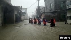 ເຈົ້າໜ້າທີ່ໜ່ວຍກູ້ໄພ ຍ່າງໃນຖະໜົນທີ່ຖືກນ້ຳຖ້ວມ ຢູ່ເມືອງ Ningde ແຂວງ Fujian ທີ່ຖືກຖະລົ່ມໂດຍພາຍຸໄຕ້ຝຸ່ນ Soudelor ປະເທດ ຈີນ. 9 ສິງຫາ 2015.