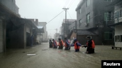 Tim penyelamat berjalan di jalan yang terendam banjir di sebuah kota yang dilanda Topan Soudelor di Ningde, provinsi Fujian, China, 9 Agustus 2015.