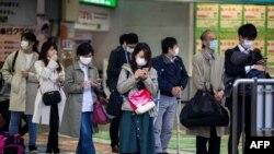 Koronavirusga qarshi yuziga niqob taqib olgan odamlar poyezd kutmoqda, Tokio, Yaponiya, 2020-yil, 6-aprel.