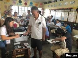 Seorang pria tua mencelupkan jarinya ke tinta setelah menyerahkan surat suaranya untuk pemilihan paruh waktu di sebuah TPS di Manila, Filipina 13 Mei 2019. (REUTERS/Jay Ereno)