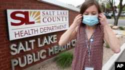 n this Tuesday, May 19, 2020, photo, health investigator Mackenzie Bray adjusts her mask at the Salt Lake County Health Department, in Salt Lake City. (AP Photo/Rick Bowmer)
