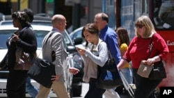 FILE - A woman sends a text message while walking across the street in San Francisco, June, 29, 2010.