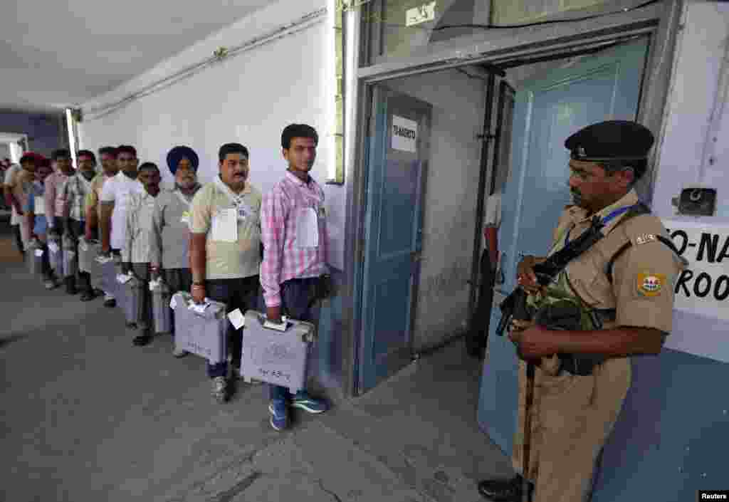 A policeman stands guard as polling officials carrying electronic voting machines arrive to count votes, in Jammu, May 16, 2014.