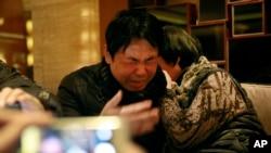 Jiang Hui (à g.) and Dai Shuqin, des parents de passagers disparus à bord du vol 370 de la Malaysian Airlines (AP)