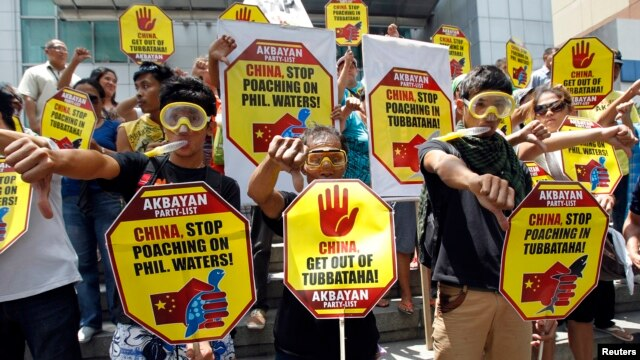 FILE - Protesters wearing snorkels and masks show the thumbs-down sign during a protest rally in front of the Chinese Consular office at the financial district of Makati city, metro Manila, April 10, 2013.