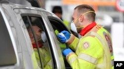 Petugas medis mengukur suhu tubuh penumpang di sebuah mobil di dekat Gries am Brenner, provinsi Tyrol Austria, perbatasan dengan Italia, 10 Maret 2020. (Foto: dok).