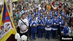 FILE - Exiled Tibetan school children sing their national anthem.