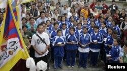 FILE - Exiled Tibetan school children sing their national anthem.