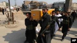 3月1日巴基斯坦一次爆炸中﹐一名政府安全被炸死﹐同僚搬運他的遺體。