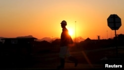 FILE - A miner returns from his shift in Nkaneng township outside the Lonmin mine in Rustenburg, northwest of Johannesburg, June 26, 2015.