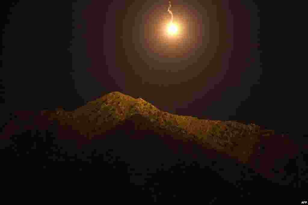 14 tháng 9: Đạn chiếu sáng rớt trên một vị trí của quân nổi dậy trong tỉnh Kunar của Afghanistan. (AP Photo/David Goldman)
