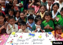 Tibetan children gather around a cake during a function organized to mark the 82nd birthday celebration of the Dalai Lama in Lalitpur, Nepal, July 6, 2017.