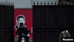 在上海,習近平畫像前帶口罩的人。(2020年2月10日)