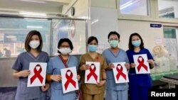Healthcare workers pose for a picture at the Ayawaddy coronavirus disease (COVID-19) treatment center in Mandalay, Myanmar February 3, 2021. Prof Cho Mar Lwin/Handout via REUTERS ATTENTION EDITORS - THIS IMAGE HAS BEEN SUPPLIED BY A THIRD PARTY. NO RESALE