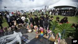 Family members from Japan place flowers at a memorial during a ceremony to commemorate the 10th anniversary of the sinking of the Ehime Maru, at the Ehime Maru Memorial in Honolulu, February 9, 2011.