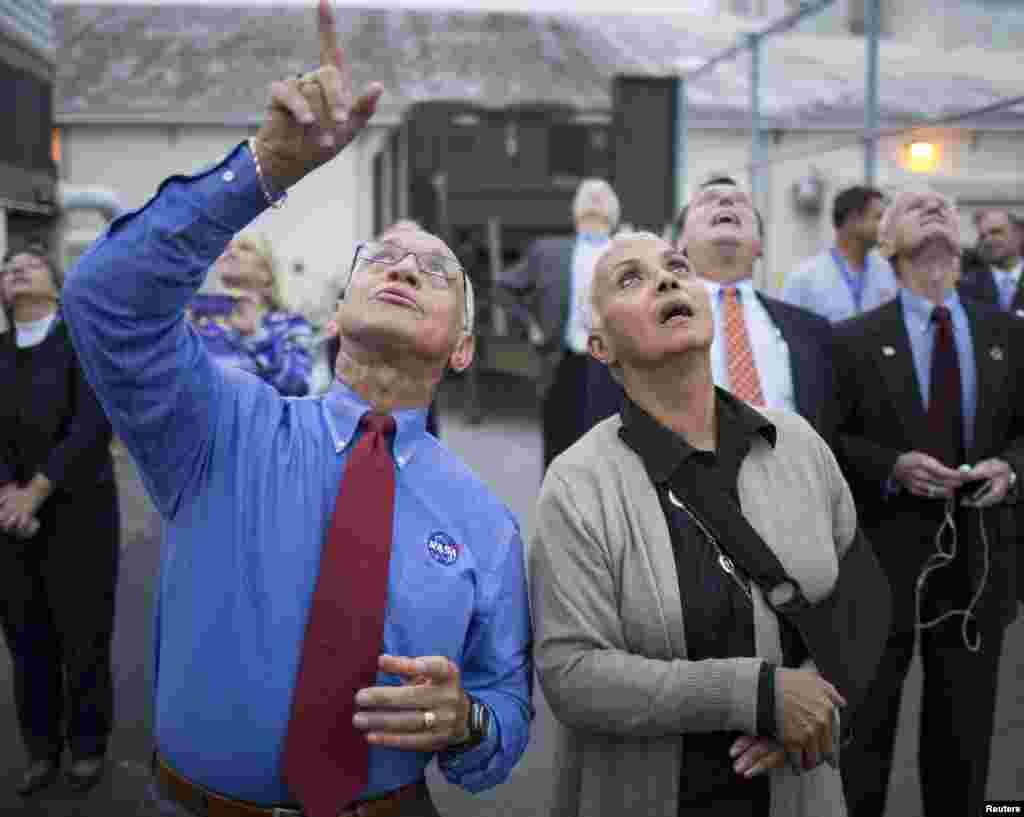 چارلز بولدن، مدیر ناسا (چپ) و همسرش جکی مسیر پرواز موشک دلتای ۴ و فضاپیمای اوریون را با نگاه دنبال میکنند – مجتمع فضاییکیپ کاناورال، فلوریدا، ۱۴ آذر