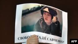 """A demonstrator holds a picture of Ukranian army officer captured by pro-Russian insurgents, Nadiya Savchenko, bearing the slogan """"Free Nadiya Savchenko"""" during a rally on Independence Square in Kiev on Jan. 26, 2015."""