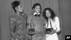 "Michael Jackson is flanked by Singer Bonnie Pointer, left, and his sister Latoya, right, at the American Music Awards in Los Angeles, Jan. 31, 1981. Jackson won two awards for favorite soul album ""Off the Wall"" and favorite male soul vocalist."