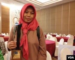 Baiq Nuril menunjukkan penghargaan Tasrif Award usai menerimanya dari AJI, Rabu (7/8/2019) malam. Tasrif Award diberikan kepada individu atau kelompok yang dinilai mendukung kebebasan berpendapat. (VOA/Rio Tuasikal)