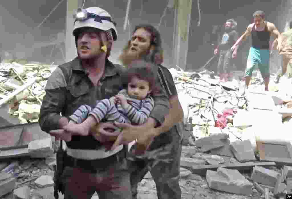 In this image made from video and posted online from Validated UGC, a civil defense worker carries a child after airstrikes hit Aleppo, April 28, 2016.