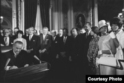 FILE - Photograph of President Lyndon Johnson signing the Voting Rights Act as Martin Luther King, Jr., with other civil rights leaders in the Capitol Rotunda, Washington, DC, Aug. 6, 1965. (Creative Commons)