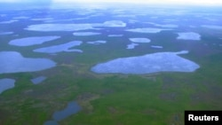FILE - An aerial view shows lakes in northeast Siberia, Aug. 28, 2007. A new study suggests that the heightened melting of Arctic permafrost could release as much as 40 billion tons of carbon into the atmosphere.