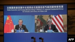 This handout photo taken Sept. 1, 2021, at an unspecified location shows a live image of U.S. climate envoy John Kerry (R) meeting via videolink with China's Foreign Minister Wang Yi (L) during Kerry's visit to Tianjin, China. (U.S. State Department)