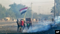 Protesters wave the national flag as security forces fire tear gas during an ongoing protest in central Baghdad, Iraq, Jan. 20, 2020.