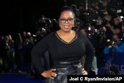 FILE - Oprah Winfrey poses for photographers at a premiere in London.