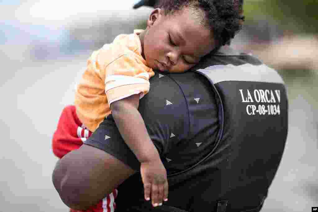 Un migrante haitiano sostiene a su hijo antes de abordar un bote hacia Capurganá.