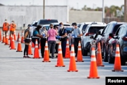Florida Department of Health medical workers prepare to administer a COVID-19 vaccine to seniors in the parking lot of the Gulf View Square Mall in New Port Richey near Tampa, Florida, Dec. 31, 2020.