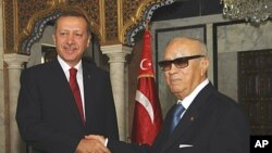 Tunisian Prime Minister Beji Caid Essebsi, right, shakes hands with his Turkish counterpart Recep Tayyip Erdogan at the prime minister office in Tunis, September 15, 2011.