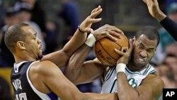 Jason Collins (à dr.) essaie de contrôler un ballon lors d'un match de la NBA entre Boston et Sacramento, le 30 jan. 2013