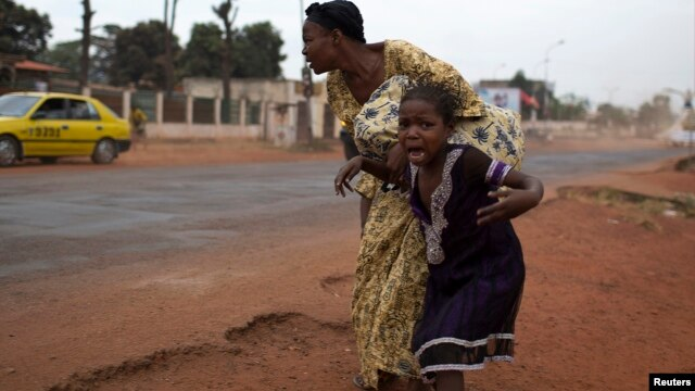 A mother holds her child while attempting to take cover as repeated gun shots are heard close to Miskine district during continuing sectarian violence in the capital Bangui, Central African Republic, Jan. 28, 2014.