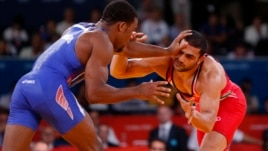 FILE - Jordan Ernest Burroughs of US (in blue) fights with Iran's Sadegh Saeed Goudarzi at the London Olympics, August 10, 2012