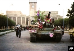 Tanks manned by Taliban fighters and decorated with flowers are shown in front of the the presidential palace, Sept. 27, 1996, in Kabul. The Islamic rebels pursued government forces Sept. 28 retreating from the devastated capital and said they had hanged two aides of the country's Soviet-era leader. The unidentified aides met the same fate as former President Najibullah and his brother, who were executed Sept. 26.