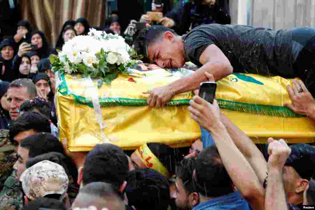 A man reacts while clenching onto the coffin of Hezbollah fighter Jalal al-Effie, who was killed during clashes in Syria's Aleppo, during his funeral in Beirut's southern suburbs, Lebanon.
