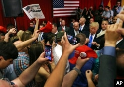 FILE - Supporters wave signs as Republican presidential candidate Donald Trump, center right, signs autographs for supporters after speaking at a campaign event on May 19, 2016, in Lawrenceville, N.J.