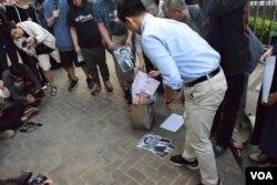 多位立法會議員焚燒中國人大委員長張德江的照片,以及中英聯合聲明,抗議北京人大釋法。(美國之音湯惠芸)