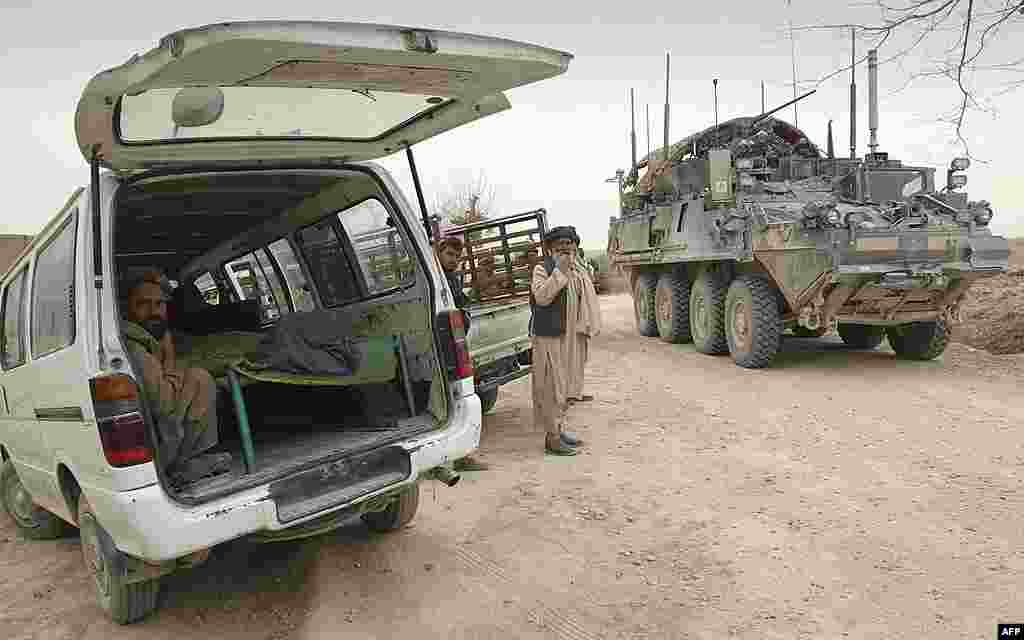 An armored military vehicle from the NATO-led International Security Assistance Force (ISAF) is seen at right, as the covered body of a person who was allegedly killed by a U.S. service member is seen inside a minibus in Panjwai. (AP)