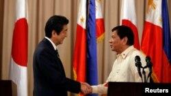 2017年1月12日,菲律宾总统杜特尔特(右)和日本首相安倍晋三在菲律宾马尼拉总统府发表联合声明后握手。